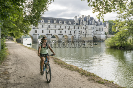 girl cycling with chenonceau castle on